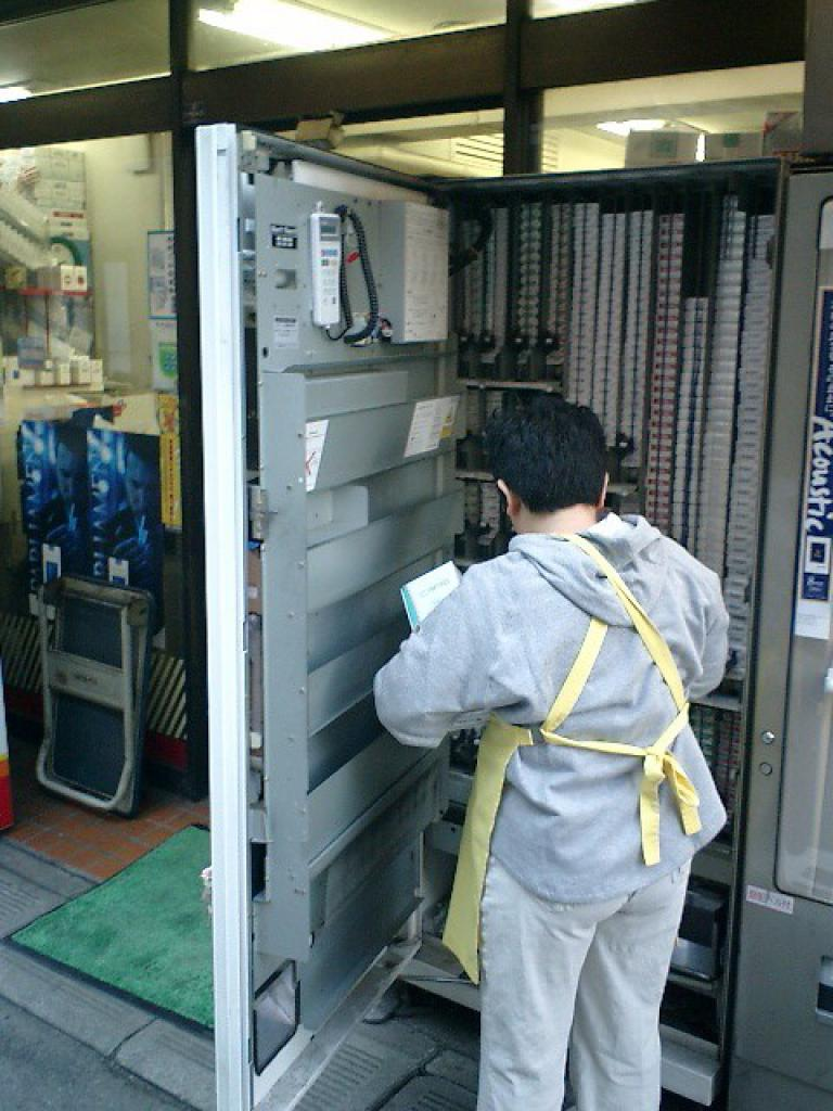 inside a cigarette vending machine in japan with vending machine servicer